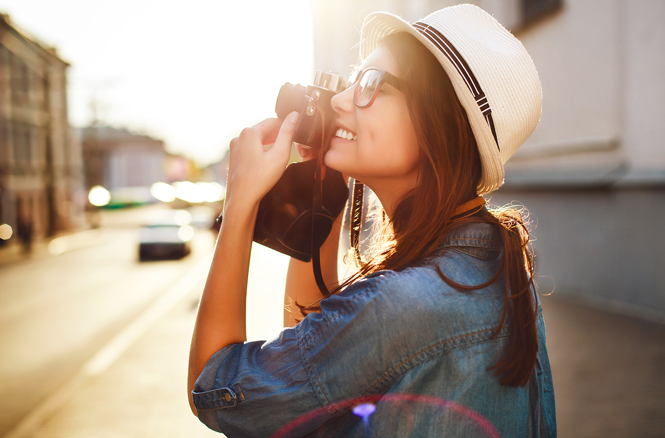 Woman holds camera to eye to take photo of building while giving real estate photography tips.