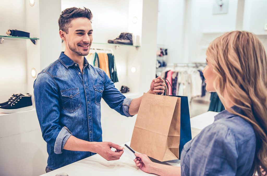 man perform exceptional customer service handing woman a bag.