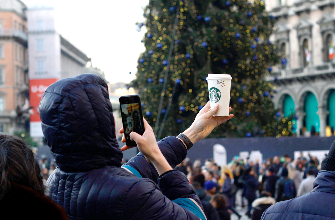 Man takes a picture of a Coffee Cup creating user generated content