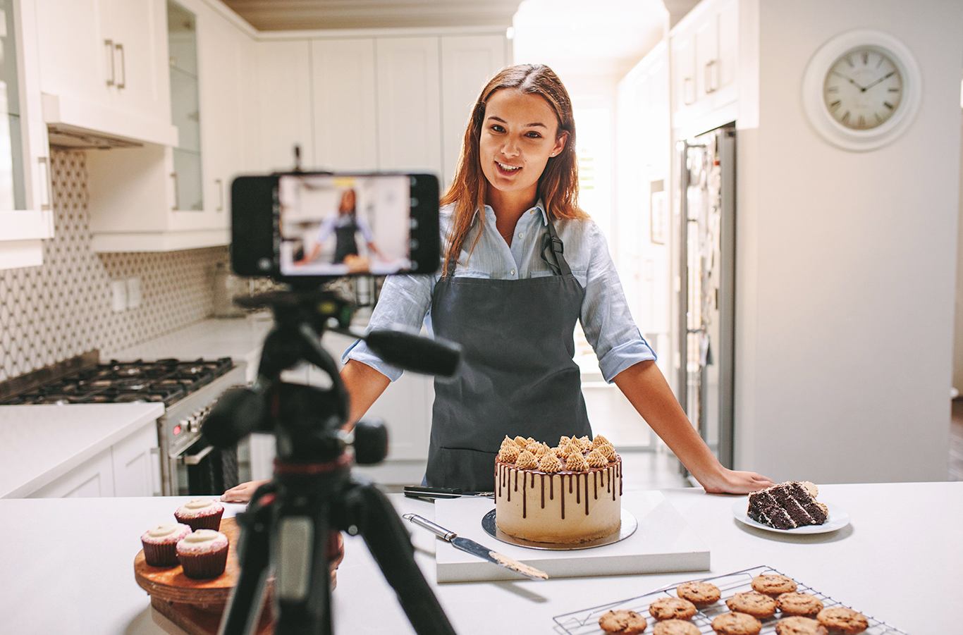 young woman uses Camera to interact with audience while baking a cake.