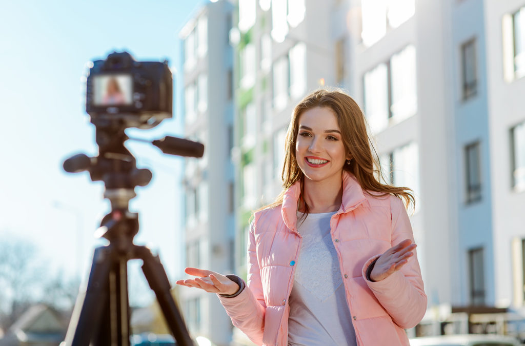 photo of a woman recording a video and deomstrating How to grow your real estate business.