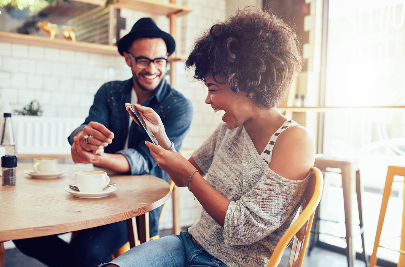 photo showing two people in a cafe laughing over a phone demonstrating ideal relationship marketing