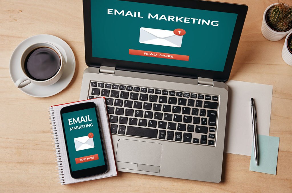image shows a phone and computer with email marketing on the screen. learn about top 3 email marketing mistakes